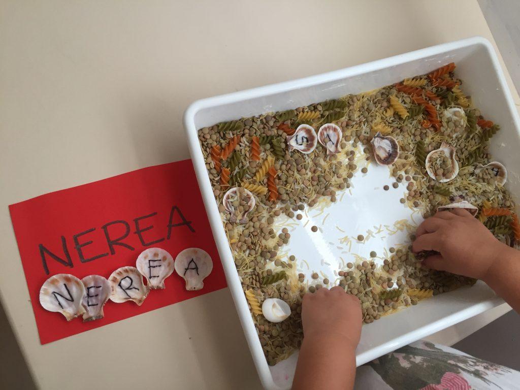 bandeja sensorial con elementos naturales para aprender las letras
